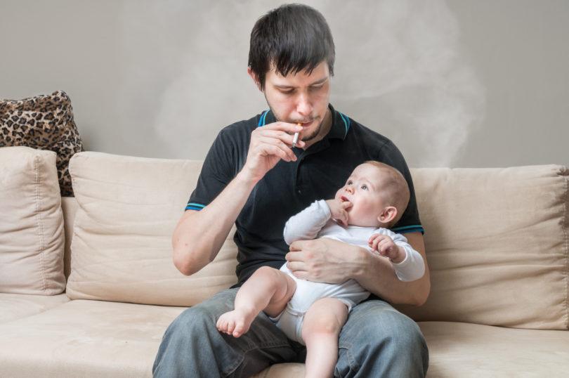 Ein Vater der Zigaretten raucht und dabei sein Baby im Arm hält
